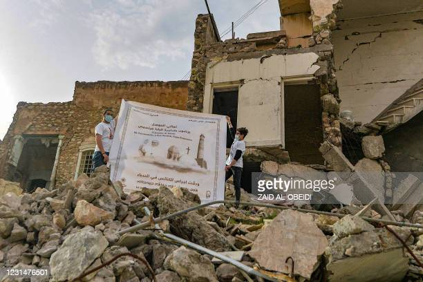 Youths unfurl a poster welcoming Pope Francis above the rubble of a destroyed house next to the ruins of the Syriac Catholic Church of the Immaculate...
