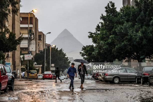 Youths walk under an umbrella during a rain storm in the Haram district of the Egyptian capital's twin city of Giza on March 12 with the pyramid of...