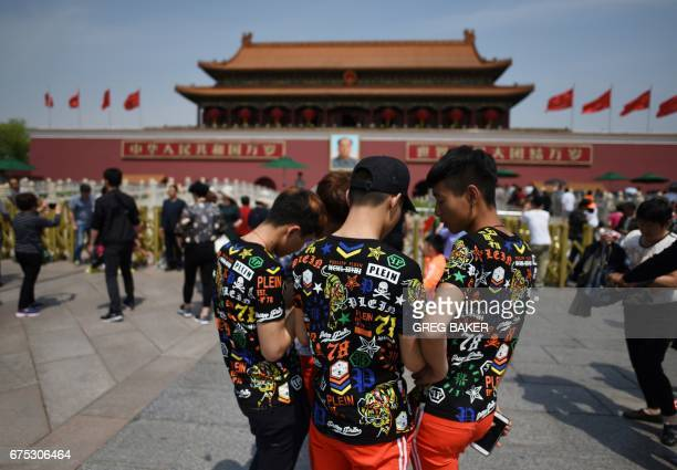 Youths wearing matching tshirts look at photos in Tiananmen Square on the May Day holiday in Beijing on May 1 2017 / AFP PHOTO / GREG BAKER