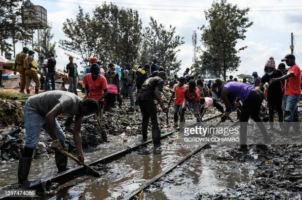 Youths who are hired by Kenyas National Youth Service remove the filthy mud from a trains tracks in the Kibera slum Nairobi on June 3 2020