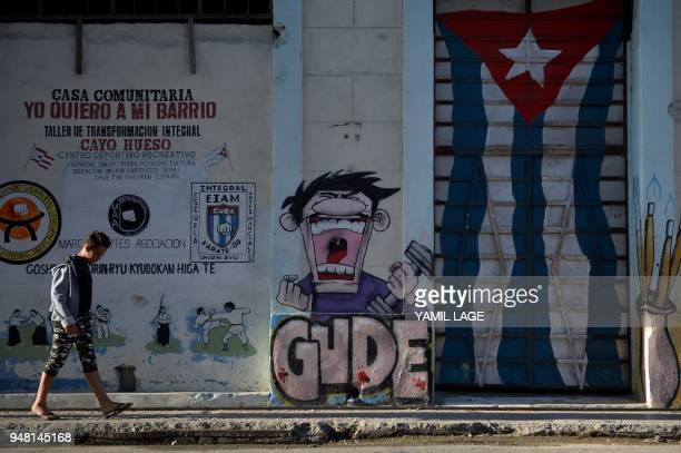 A youung man walks along a street in Havana on April 18 2018 as the National Assembly holds a session that will select Cuba's Council of State ahead...