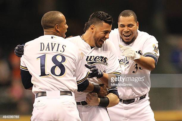 Yovani Gallardo of the Milwaukee Brewers celebrates with Khris Davis and Wily Peralta after hitting a walk off double in the bottom of the eleventh...