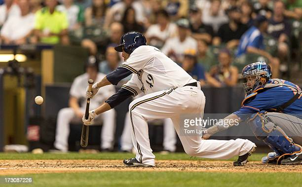 Yovani Gallardo of the Milwaukee Brewers lays down a bunt against the New York Mets and reaches safely on an error during the sixth inning at Miller...