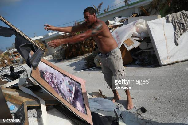 Yoyi Hinojosa throws items out as he cleans up his home that was badly damaged by hurricane Irma on September 19 2017 in Marathon Florida The process...