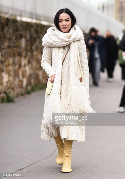 Yoyo Cao is seen wearing a cream sweater dress, cream scarf and yellow boots outside the Loewe show during Paris Fashion Week: AW20 on February 28,...