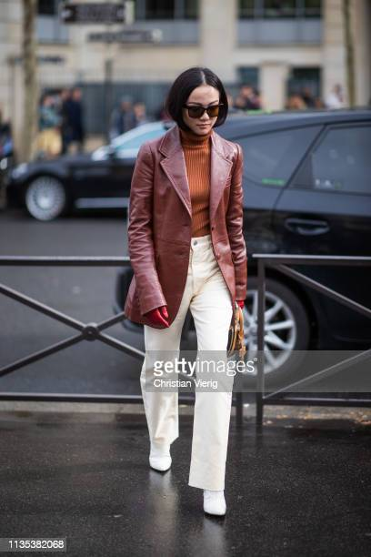 Yoyo Cao is seen wearing brown coat orange turtleneck white pants outside Miu Miu during Paris Fashion Week Womenswear Fall/Winter 2019/2020 on March...