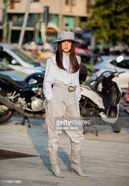 Yoyo Cao is seen wearing hat, white blouse, high waist pants, boots outside the Alberta Ferretti show during Milan Fashion Week Spring/Summer 2020 on...