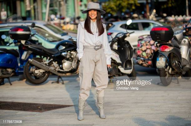 Yoyo Cao is seen wearing hat white blouse high waist pants boots outside the Alberta Ferretti show during Milan Fashion Week Spring/Summer 2020 on...