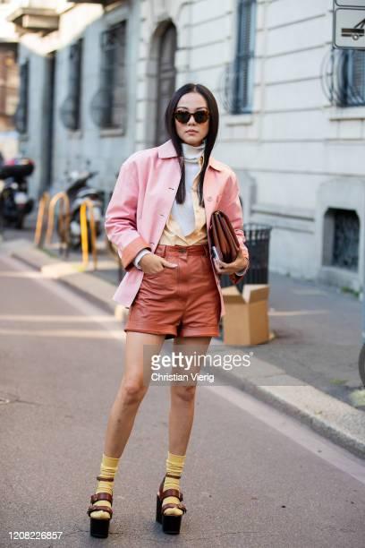 Yoyo Cao is seen wearing pink jacket, brown shorts, bag, turtleneck, platform sandals, yellow socks outside Ferragamo during Milan Fashion Week...