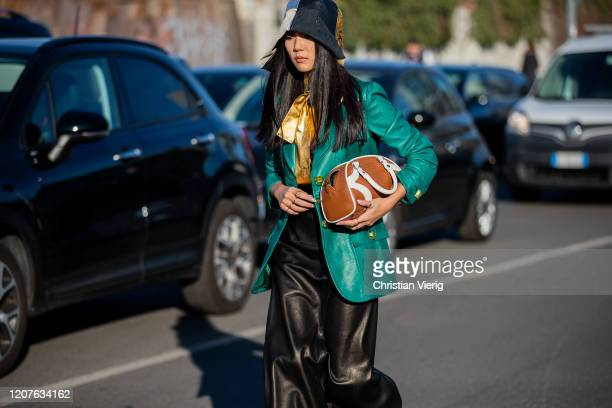 Yoyo Cao is seen wearing two tone hat brown bag green jacket black skirt outside Prada during Milan Fashion Week Fall/Winter 20202021 on February 20...