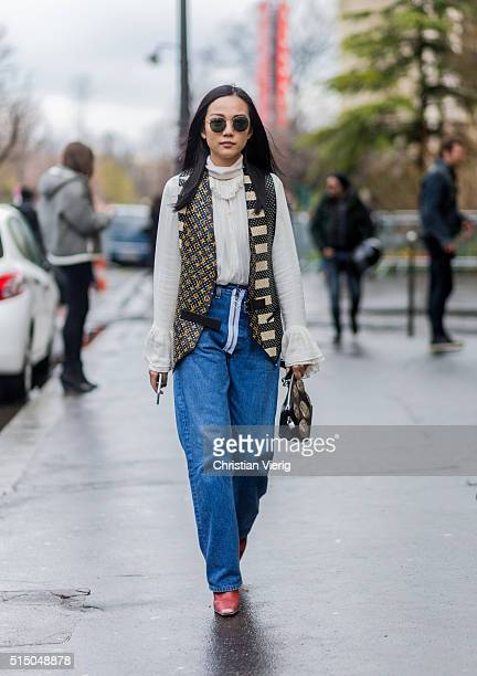Yoyo Cao is wearing a creme blouse a vest and denim jeans outside Moncler Gamme Rouge during the Paris Fashion Week Womenswear Fall/Winter 2016/2017...