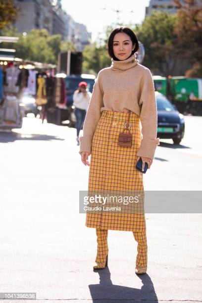 Yoyo Cao wearing a beige sweater a checked midi skirt and matching checked boots is seen before the Rochas show on September 26 2018 in Paris France