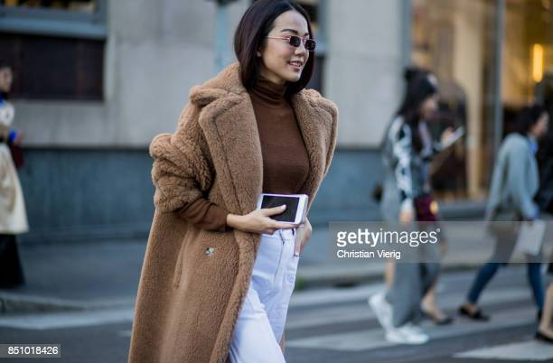 Yoyo Cao wearing a brown teddy coat white pants white heels brown turtleneck is seen outside Max Mara during Milan Fashion Week Spring/Summer 2018 on...