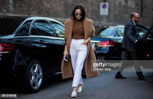 Yoyo Cao wearing a brown teddy coat white pants white heels brown turtleneck is seen outside Max Mara during Milan Fashion Week Spring/Summer 2018 on...