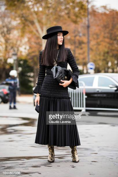Yoyo Cao wearing a long black dress Chanel necklace printed boots Chanel black bag and black hat is seen before the Chanel show on October 2 2018 in...
