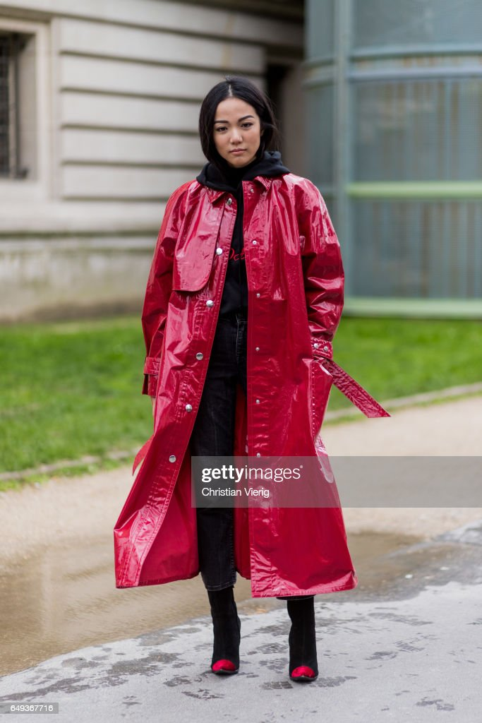 Yoyo Cao wearing a red coat, denim jeans, ankle boots, hoody outside Moncler on March 7, 2017 in Paris, France.