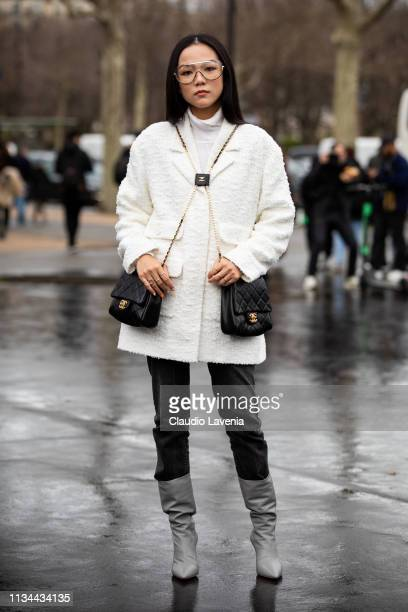Yoyo Cao wearing a white turtleneck top black jeans grey boots white coat and two black Chanel bag is seen outside Chanel on Day 9 Paris Fashion Week...