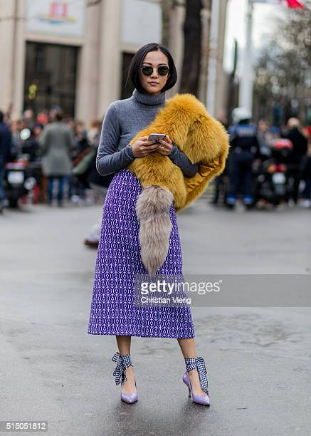 Yoyo Cao wearing a yellow fur scarf and grey turtleneck and purple skirt outside Miu Miu during the Paris Fashion Week Womenswear Fall/Winter...