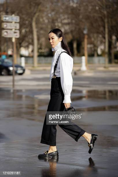 Yoyo Cao wearing Chanel white blouse, black pants with shoulder strap, black pants, patent shoes and mini Chanel bag outside the Chanel show during...