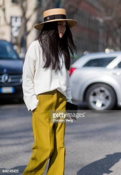 Yoyo Cao wearing mustard wide leg pants white turtleneck straw hat outside Armani during Milan Fashion Week Fall/Winter 2017/18 on February 27 2017...