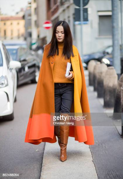 Yoyo Cao wearing orange yellow red cape orange turtleneck denim jeans overknees is seen outside Bottega Veneta during Milan Fashion Week...