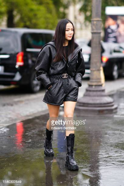 Yoyo Cao wears a black leather dress, a Chanel belt, black leather boots, outside Chanel, during Paris Fashion Week - Womenswear Spring Summer 2020,...