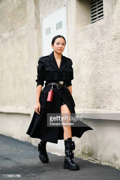 Yoyo Cao wears a black long coat a belt a red attached water flask metallic bottle outside the Prada show during Milan Fashion Week Spring/Summer...