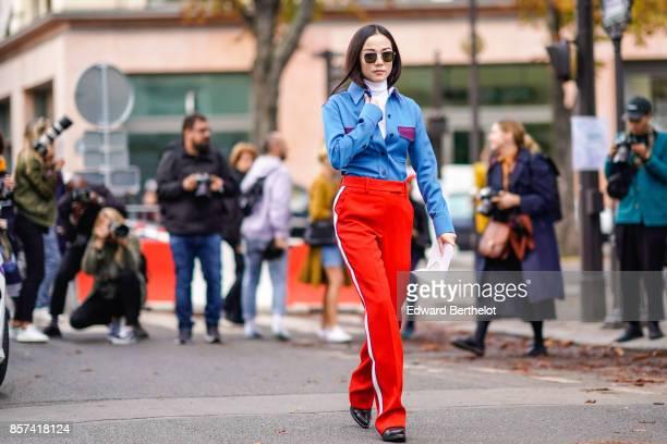Yoyo Cao wears a blue jacket red sportswear pants outside Moncler during Paris Fashion Week Womenswear Spring/Summer 2018 on October 3 2017 in Paris...