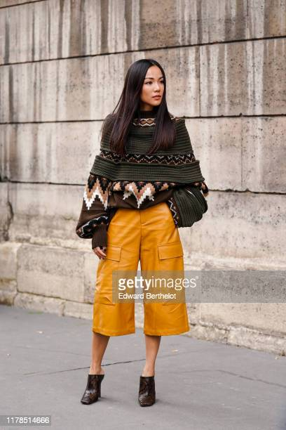 Yoyo Cao wears a brown, ochre-yellow and white geometric pattern sweater, saffron-color leather short pants, brown python pattern shoes, outside...