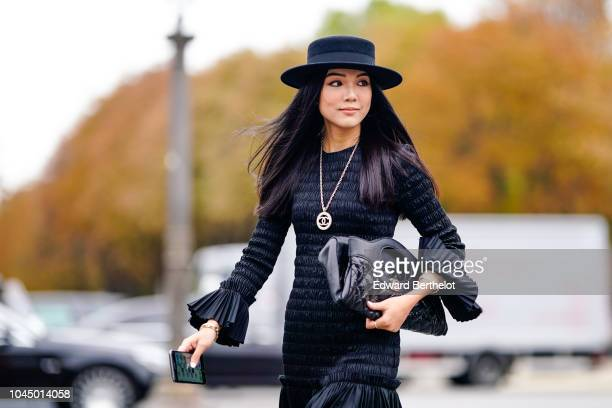 Yoyo Cao wears a hat, a Chanel necklace, a black puffer bag, a pleated skirt, golden boots, outside Chanel, during Paris Fashion Week Womenswear...