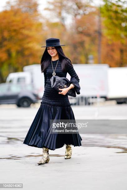Yoyo Cao wears a hat a Chanel necklace a black puffer bag a pleated skirt golden boots outside Chanel during Paris Fashion Week Womenswear...