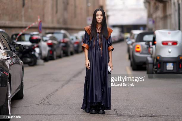 Yoyo Cao wears a navy blue dark long pleated dress with brown leather shoulder pads, outside Sportmax, during Milan Fashion Week Fall/Winter...