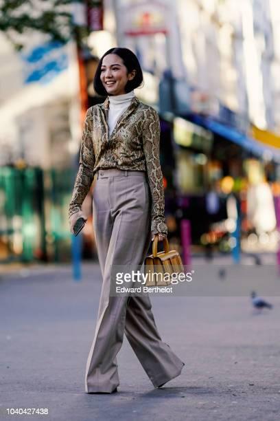 Yoyo Cao wears a snake print shirt, a yellow bag, gray flare pants, outside Koche, during Paris Fashion Week Womenswear Spring/Summer 2019, on...