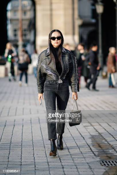 Yoyo Cao wears a studded bomber jacket with printed features black denim jeans a Vuitton bag black leather shoes sunglasses outside Louis Vuitton...