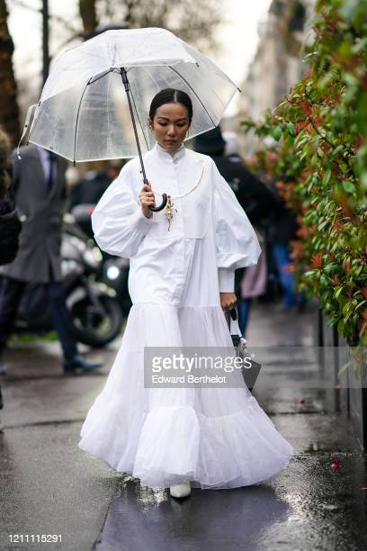 Yoyo Cao wears a white dress/shirt with puff sleeves, a mesh bottom ruffled and pleated part, mandarin collar, a turtleneck wool pullover, a golden...