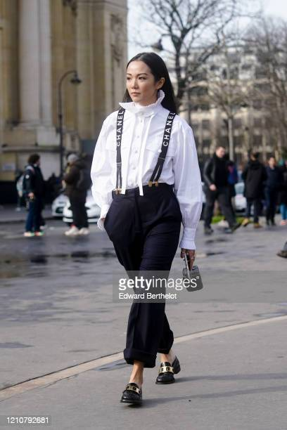 Yoyo Cao wears a white shirt, Chanel straps, navy blue pants, black leather shoes, a quilted mini Chanel bag, outside Chanel, during Paris Fashion...