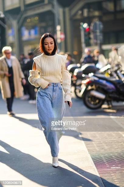 Yoyo Cao wears a white wool pullover, large pale blue denim pants, white boots, outside Philosophy, during Milan Fashion Week Fall/Winter 2020-2021...