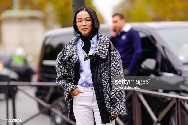 Yoyo Cao wears glasses a pattern wool jacket white pants a blue shirt white shoes outside Miu Miu during Paris Fashion Week Womenswear Spring/Summer...