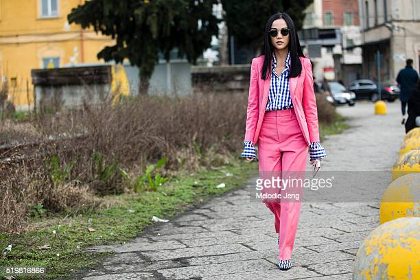 Yoyo Cao wears RayBan sunglasses a pink Gucci suit with Gucci white and blue gingham shirt and loafers at the Gucci show during the Milan Fashion...