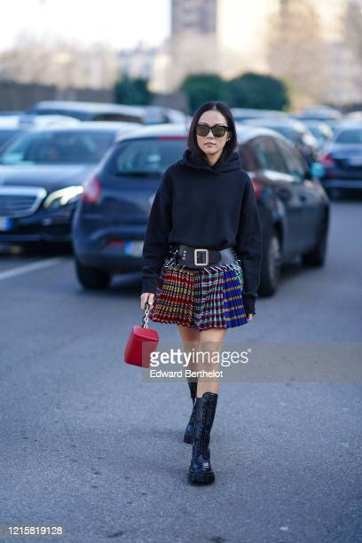 Yoyo Cao wears sunglasses, a black hooded sweatshirt, a black belt, a colorful pleated mini skirt, a red bag, black Prada mid-calf lace-up platform...