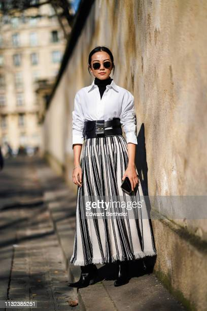 Yoyo Cao wears sunglasses, a white shirt, a large black leather belt, a black and white striped skirt, outside Dior, during Paris Fashion Week...