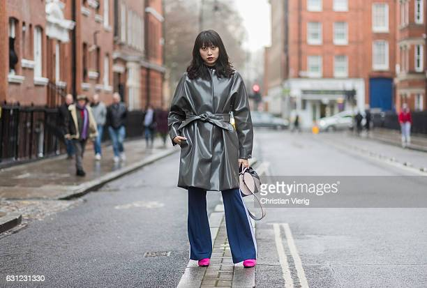 Yoyo Lu wearing a latex grey coat flared pants pink shoes during London Fashion Week Men's January 2017 collections at JW Anderson on January 8 2017...