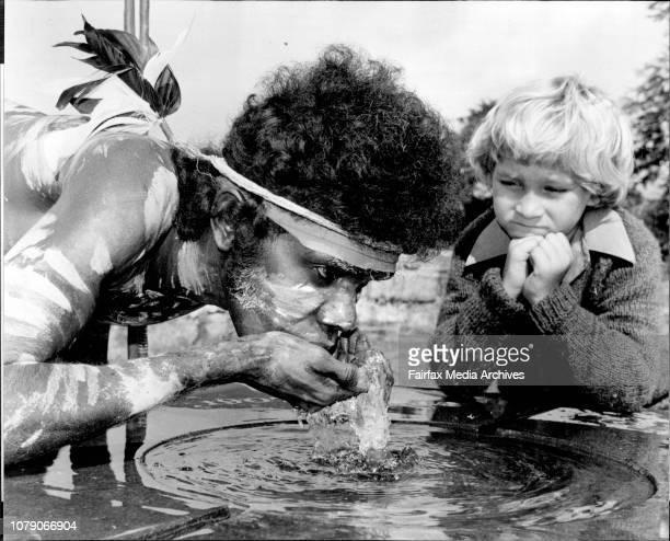 5 yr old Chris DeBattista from Riley St Infants school watches whilst Bobby Bumumgur a songman from the Ramangining Performers takes a drink from the...