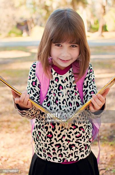 7 yr old girl holding a big book open