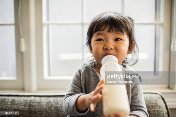 2 yr old girl with baby bottle - milk bottle stock pictures, royalty-free photos & images