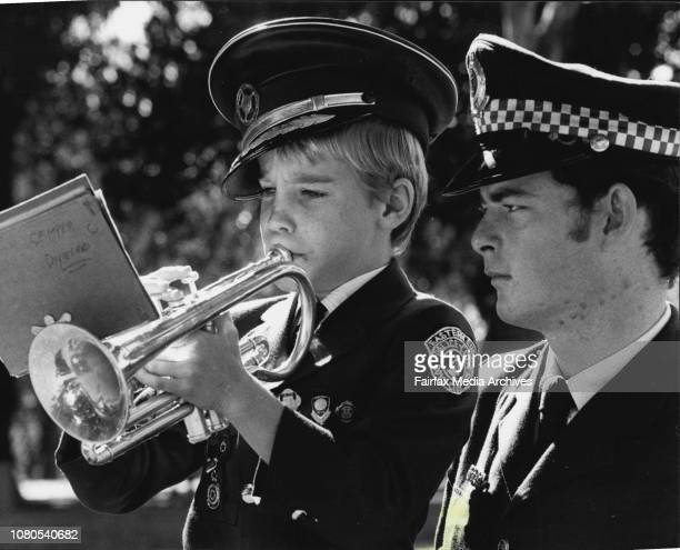 9 yr old Malcolm Rennex from the Eastern Suburbs Police Citizens Boys Club practices on his cornet before taking part in the march He is watched by...