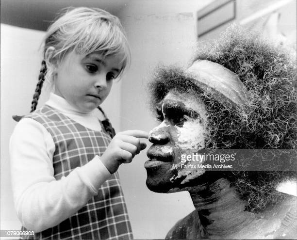 5 yr old Samantha Bennett from Riley St Infants School helps David Dalbugarri a songman from the Ramangining Performers apply white ochre to his...