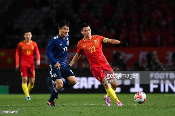 Yu Dabao of China and Yasuyuki Konno of Japan compete for the ball during the EAFF E1 Men's Football Championship between Japan and China at...