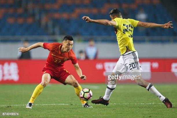 Yu Dabao of China National Team and Giovanni Moreno of Columbia National Team compete for the ball during the international friendly match between...