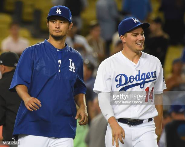 Yu Darvish and Enrique Hernandez of the Los Angeles Dodgers head on to the field after the game against the Chicago White Sox at Dodger Stadium on...